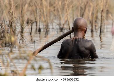 GANVIE, BENIN - JAN 11, 2017: Unidentified Beninese man swims in  the lake Nokwe. Benin people suffer of poverty due to the bad economy.