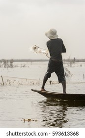 GANVIE, BENIN - JAN 11, 2017: Unidentified Beninese fisher man throws a net sails in a wooden boat over the lake Nokwe. Benin people suffer of poverty due to the bad economy.