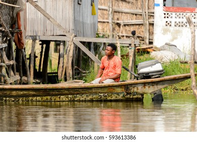 GANVIE, BENIN - JAN 11, 2017: Unidentified Beninese man sails in a wooden boat in a village over the lake Nokwe. Benin people suffer of poverty due to the bad economy.