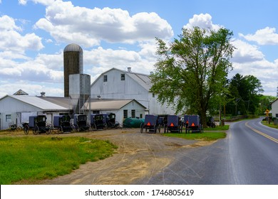Gap, PA, USA / June 1, 2020: A number of Amish buggies parked at a barn on Pentacostal Day so the faithful can participate in worship service.