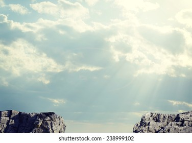 Gap in rocky pathway or chasm between two rocks. Sky and clouds as backdrop