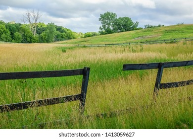 Gap in weathered old wooden equine fence around onetime pasture gone to seed on a cloudy morning in summer, northern Illinois, USA, for themes of perimeters, discontinuity, and age (foreground focus)