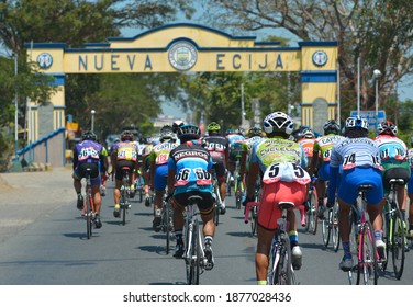 Gapan, Nueva Ecija, Philippines - Feb 2017: A peloton of riders at the highway enters Nueva Ecija from Bulacan. A welcome arch marks the boundary crossing. A road bicycle race.