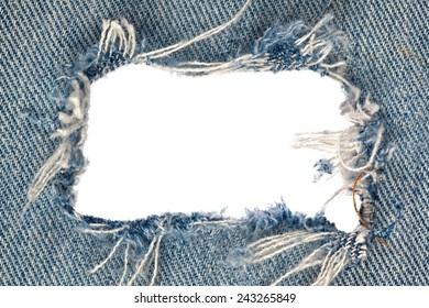 A gaping hole with ragged edges in denim jeans, horizontal.