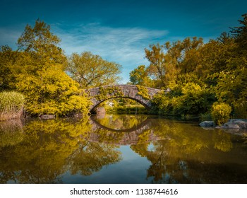 Gapstow bridge in Central Park in autumn reflecting in the water