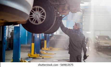 Garage automobile service - a mechanic checks the transmission