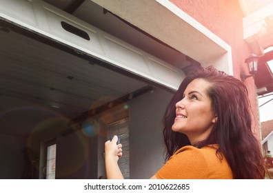 Garage door PVC. Girl or young woman use remote controller for closing and opening garage d