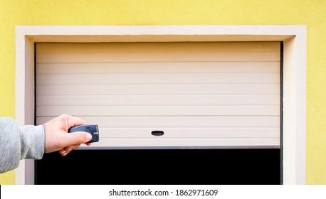 Garage door PVC. Hand use remote controller for closing and opening garage door