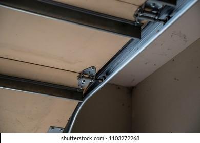Garage door track wheels hinge close up industrial metal inside open close