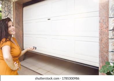 Garage door. Young woman holding remote controller and opening garage door