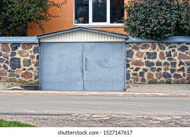 garage with gray metal gates and a stone fence on the street by an asphalt road