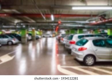 Garage interior blurred. Car lot parking space in underground city garage. Empty road asphalt background in soft focus. Large private garage