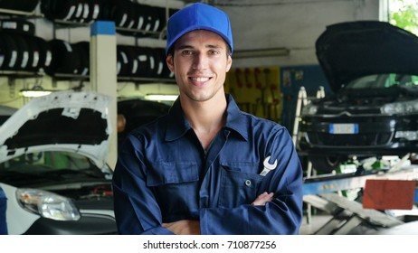 In a garage, a mechanic after having checked and checked the oil and engine at the car smiles because the car has been repaired successfully. Concept of: security,safety, insurance and professionalism