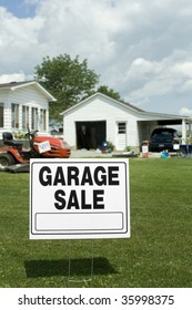 A garage sale sign with garage and items in background. Room for copy.