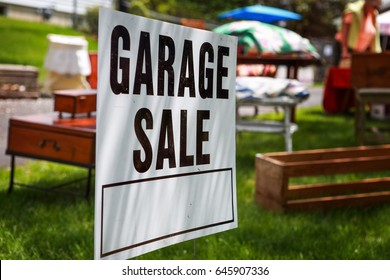Garage sale sign on the shady lawn of a suburban home, shallow focus in center of sign
