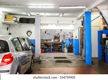 Garage service workshop with tools, hydraulic platform elevator, tools, equipment and car detail