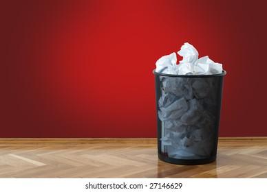 Garbage bin full of crumpled papers
