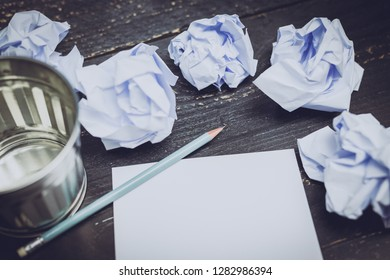 garbage bin on desk setting with pencil notepad and scrunched paper balls, concept of drafting and struggling to write documents