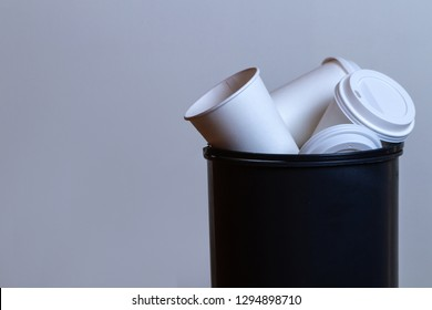 Garbage bin overflowing with paper, coffee cups. Coffee addiction and drinking a lot cups of coffee. Copy space
