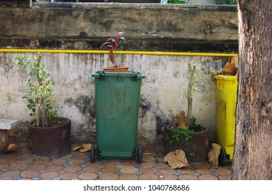 garbage bin stands in front of wall