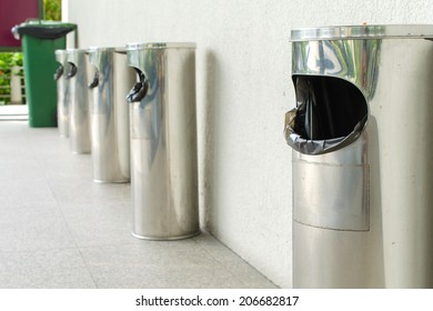 Garbage bin of steel stainless outside a building.