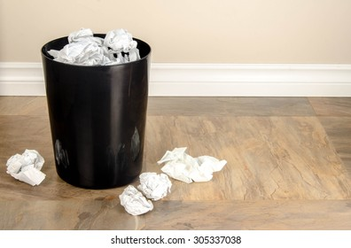 A garbage can with lots of crumpled paper in and around it signifying frustration or writers block