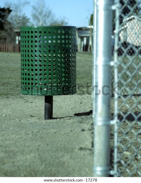 A garbage can near a ball park