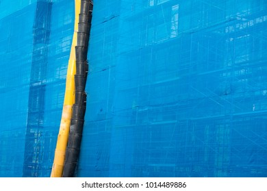Garbage chute on the exterior of an office building, with blue tarps covering scaffolding, at an industrial construction project