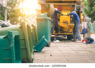 Garbage collector on the garbage truck.Sweeper or Worker are loading waste into the garbage truck carrier.
