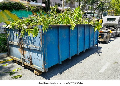 Garbage container bin latch with truck full of garden refuse, woods, chopped trees for disposal