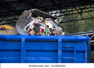 A garbage container. A large black container filled with debris. Bags of garbage of different colors and a mountain rise above the container. There