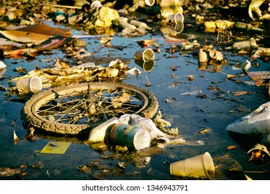 Garbage dump partially immersed in water. Incivility concept.