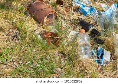 Garbage in forest. People illegally throw garbage into forest. Illegal garbage dump in nature. Dirty environment garbage polluting near footpath in forest. Rubbish, trash