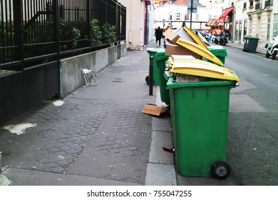 Garbage litter bin full with boxes and rubbish in front of resident and side walk in Paris