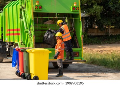 Garbage man working together on emptying dustbins for trash removal.