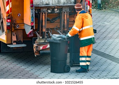 Garbage men collecting the bins in the street