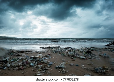 Garbage on beach, environmental pollution in Bali Indonesia. Storm is coming on background. And drops of water are on camera lens. Dramatic view