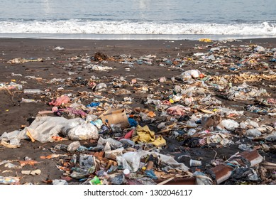 Garbage on a sandy polluted beach (plastic bags, bottles, cigarettes, trash). Ende, Flores island, Indonesia