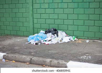 Garbage pile on street in front of green wall