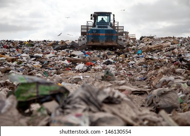 Garbage piles up in landfill site each day while truck covers it with sand for sanitary purpose