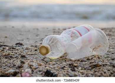 Garbage is a plastic bottle and plastic glass on the beach.