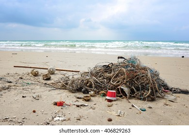 Garbage, plastic, wood and trawl on the beautiful beach