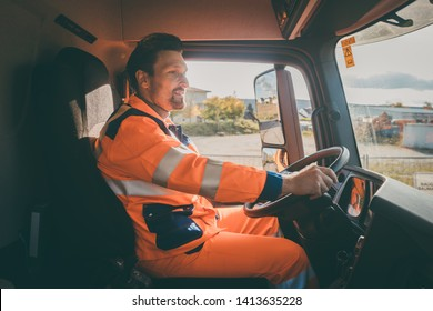 Garbage removal worker in protective clothing driving a dump truck