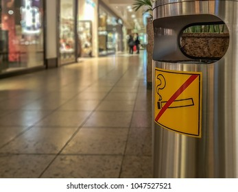 Garbage is at a shopping center with a sign on it that prohibits smoking. Concept: cleanliness