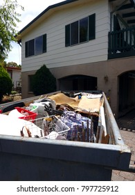 Garbage skip in a front yards of a family suburban home full of waste