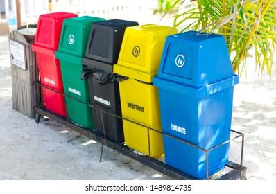 Garbage trash bins for waste segregation. Separate waste collection food waste, infection, biodegradable, non biodegradable and recycle trash bin. Multicolor trash bin on a sandy beach under coconut.