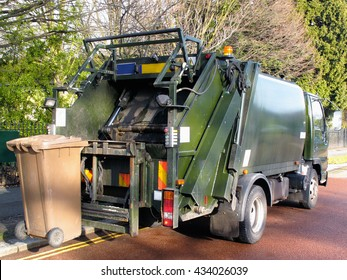 Garbage truck with a bin at the rear