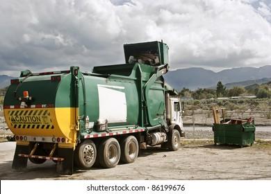 Garbage truck caught in action disposing trash.