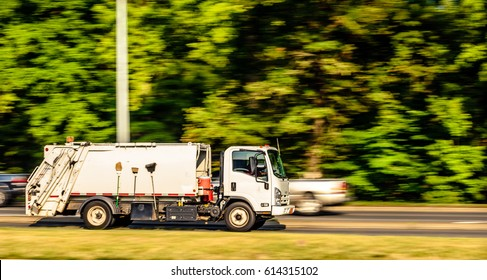A garbage truck is running down the highway captured early morning during summer season. This image was captured using panning technique to blur the background and emphasize motion.