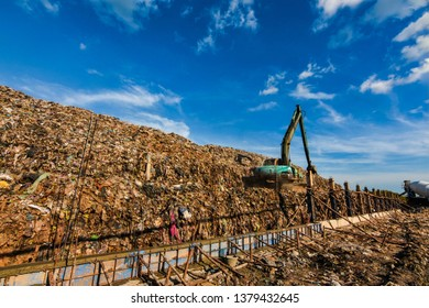 Garbage truck is working in the heat. Stink and smoke on the mountain garbage. Large garbage collection from urban and industrial areas. It is a fast-paced and difficult-to-dispose garbage